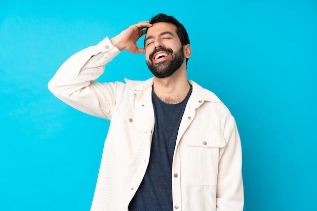 Jeune bel homme avec veste en velours côtelé blanc sur mur bleu isolé souriant beaucoup