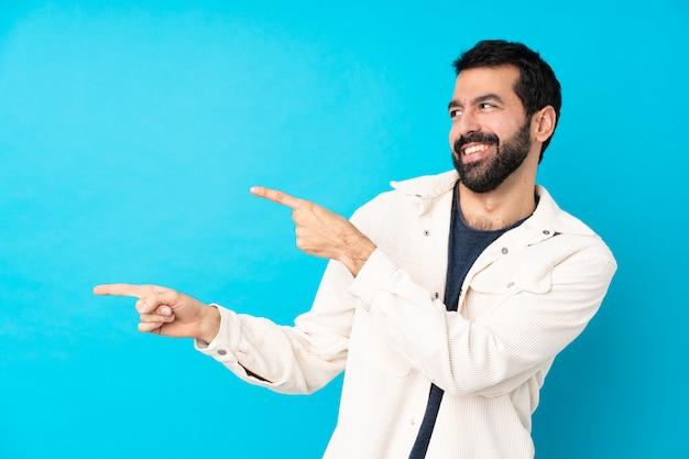 Jeune bel homme avec une veste en velours côtelé blanc pointant le doigt sur le côté et présentant un produit