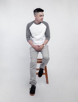 Jeune bel homme vêtu d'un t-shirt raglan gris blanc était assis dans une chaise