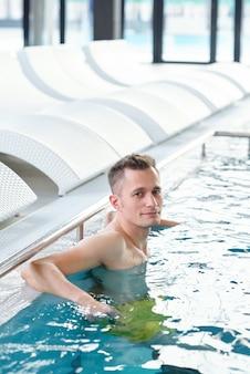 Jeune bel homme vous regarde en se tenant debout dans une eau transparente bleue au bord de la piscine avec une rangée de transats derrière