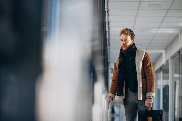 Jeune bel homme voyageant avec sac