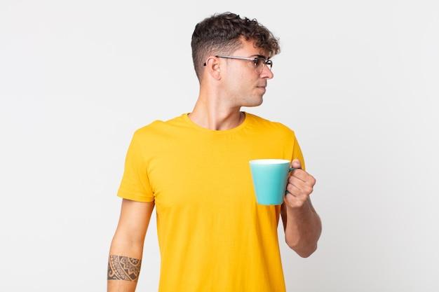 Jeune bel homme sur la vue de profil pensant, imaginant ou rêvant et tenant une tasse de café