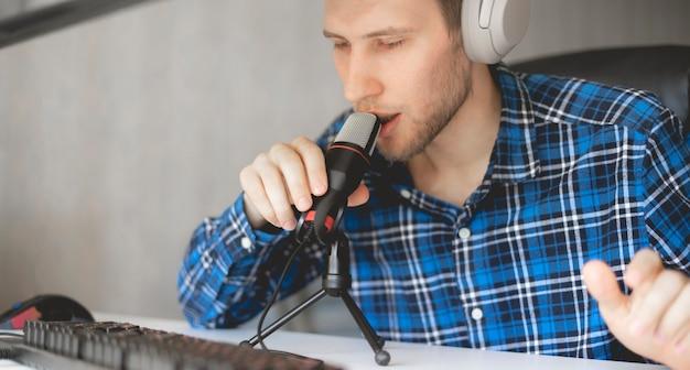 Un jeune bel hôte masculin enregistrant un podcast en studio, diffusé en direct