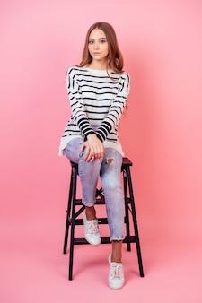 Jeune et belle adolescente écolière posant assis sur une chaise en studio sur fond rose