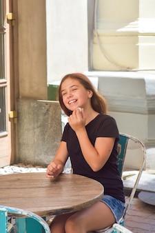 Jeune belle adolescente mangeant des bonbons à la noix de coco sur la terrasse