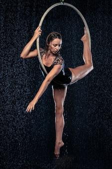 Jeune belle artiste de cirque mince faisant des performances avec cerceau aérien posant sur un fond de studio aqua noir.
