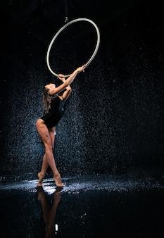 Jeune belle artiste de cirque mince tenant un cerceau aérien posant sur un fond de studio aqua noir.