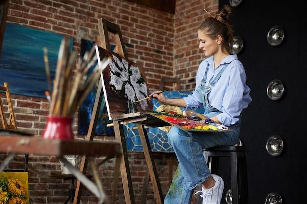 Jeune belle artiste féminine peignant la nature morte avec du tournesol sur toile à l'aide de peintures à l'huile et d'un pinceau d'art. peintre créant des œuvres d'art dans un studio d'art. détente, loisirs, hobby, gestion du stress.
