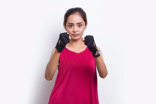 Jeune belle asiatique sportive montrant le geste du poing sur fond blanc