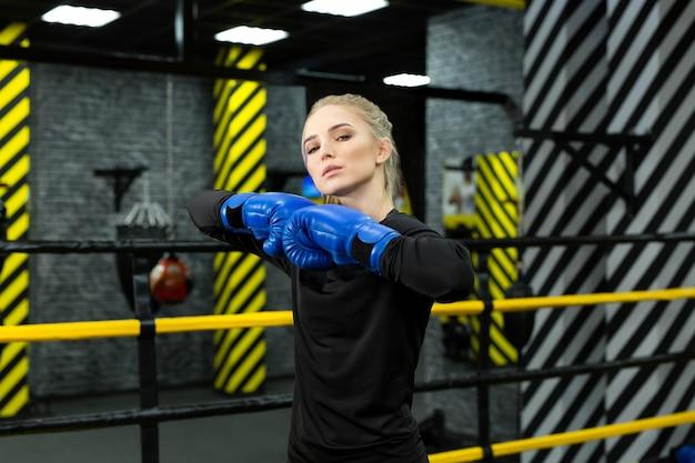 Jeune belle athlète en gants de boxe bleus pose dans le ring