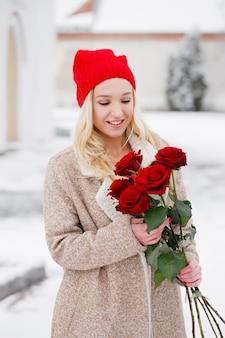 Jeune belle blonde avec bouquet de roses rouges le jour de la saint-valentin