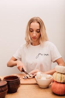 Jeune belle blonde coupe des champignons sur la table dans la cuisine