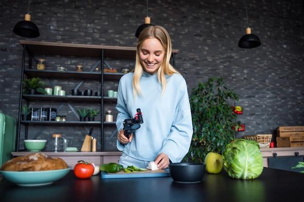 Jeune belle blonde prend des vidéos pendant qu'elle cuisine dans la cuisine