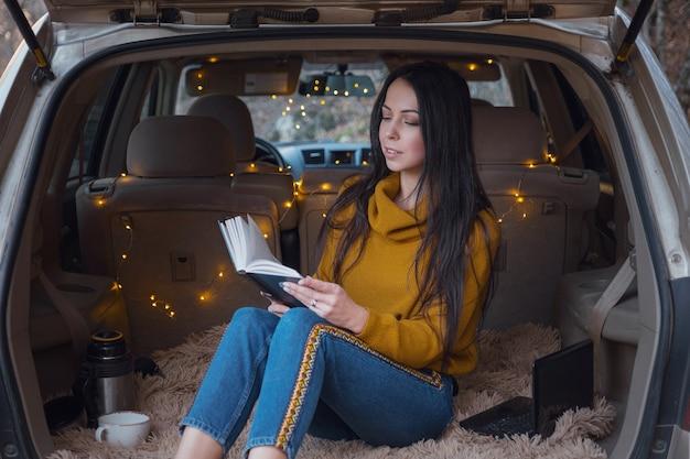 La jeune belle brune aime se détendre dans le coffre de sa voiture. une guirlande jaune et un plaid beige créent le confort, femme lisant un livre et buvant du thé chaud