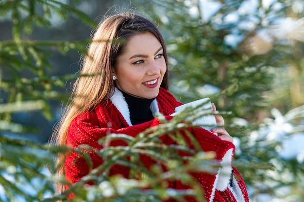 Une jeune et belle brune avec un plaid rouge sur son épaule et une tasse de thé dans ses mains dans les bois entre les arbres de noël enneigés