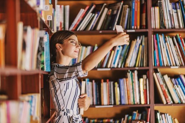 Jeune belle brune en robe et avec des lunettes tenant un livre et prenant selfie en se tenant debout dans la bibliothèque.