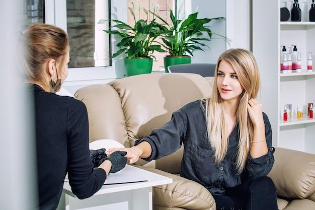 Jeune belle cliente de femme fait une manucure avec un maître de manucure professionnel dans un salon de beauté