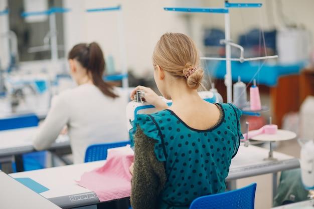 Jeune belle couturière coud sur machine à coudre en usine