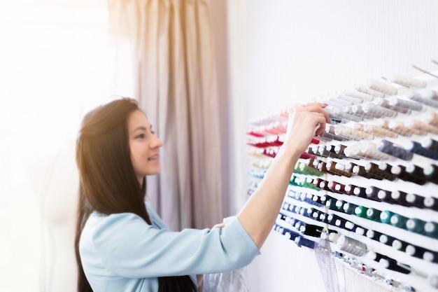 Jeune belle couturière à la recherche de fils pour tissus sur son lieu de travail.