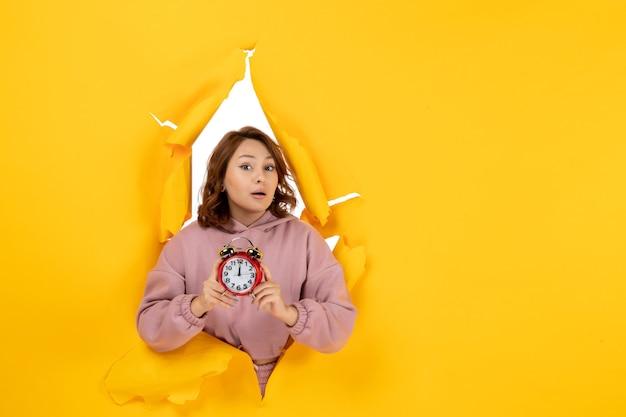 Jeune belle dame confuse montrant l'horloge sur fond de percée déchiré jaune