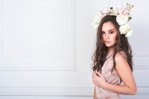 Jeune belle dame en robe avec des fleurs fraîches sur la tête