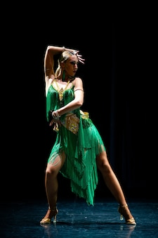 Jeune belle danseuse blonde posant sur fond noir studio