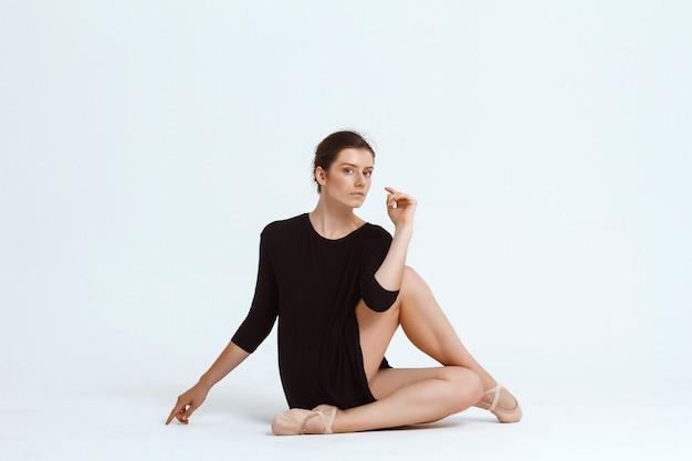 Jeune belle danseuse contemporaine posant sur mur blanc. copiez l'espace.