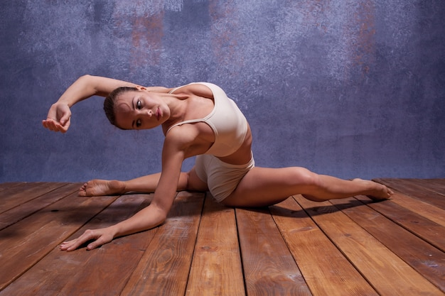 Jeune belle danseuse en maillot de bain beige dansant sur fond lilas