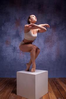 Jeune belle danseuse en maillot de bain beige posant sur un cube blanc sur fond de studio lilas
