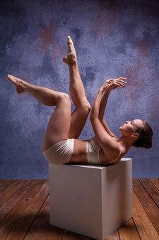 Jeune belle danseuse en maillot de bain beige posant sur cube blanc
