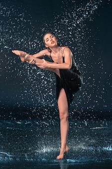 La jeune belle danseuse moderne dansant sous les gouttes d'eau dans le studio bleu aqua