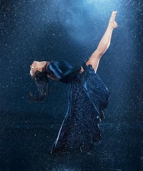Jeune belle danseuse moderne dansant sous des gouttes d'eau