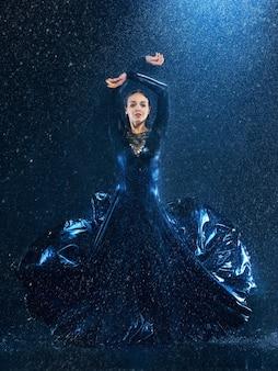 Jeune belle danseuse moderne dansant sous les gouttes d'eau