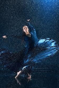 La jeune belle danseuse moderne en robe longue danse sous des gouttes d'eau dans un studio bleu aqua