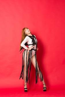 Jeune belle danseuse posant dans un mur rouge