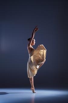 Jeune belle danseuse en robe beige dansant sur fond gris