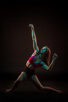 Jeune belle danseuse en robe beige danse sur fond noir