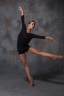 Jeune belle danseuse de style moderne posant sur fond gris