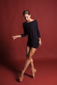 La jeune belle danseuse de style moderne posant sur un fond rouge de studio