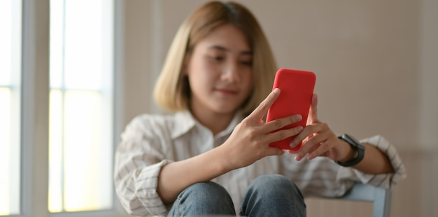 Jeune belle designer féminine regardant un smartphone et assise sur une chaise