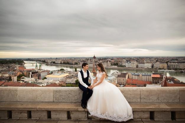 Jeune belle et élégante paire de jeunes mariés assis près du bastion des pêcheurs à budapest, hongrie