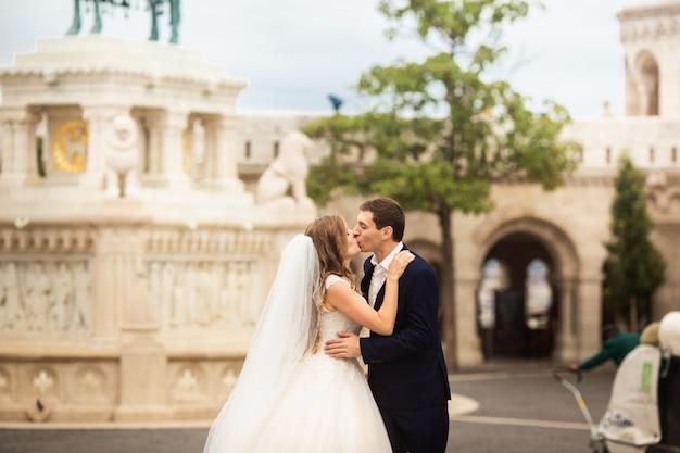 Jeune belle et élégante paire de jeunes mariés marchant près du bastion des pêcheurs à budapest, hongrie