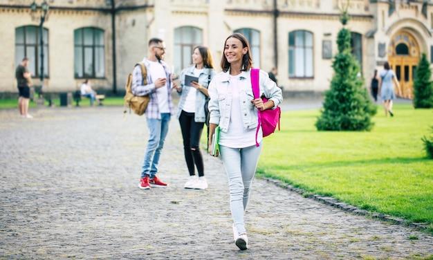 Jeune belle étudiante brune en vêtements en jean avec sac à dos et livres en mains est debout sur un groupe de ses amis étudiants