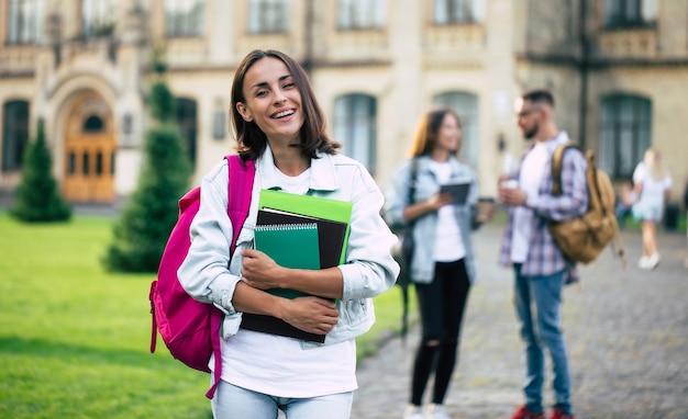 Jeune belle étudiante brune en vêtements en jean avec sac à dos et livres en mains sur un groupe de ses amis étudiants
