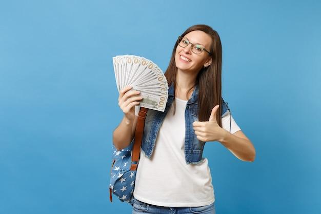 Jeune belle étudiante heureuse dans des verres avec sac à dos montrant le pouce vers le haut tenant beaucoup de dollars, argent comptant isolé sur fond bleu. éducation dans le concept de collège universitaire secondaire.