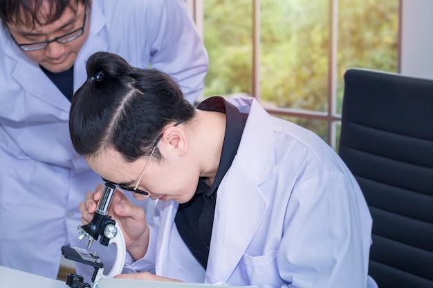 Jeune belle étudiante en médecine et assistante de recherche avec microscopes