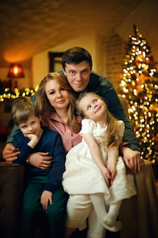 Jeune belle famille avec deux enfants posant sur une chaise dans un intérieur de noël