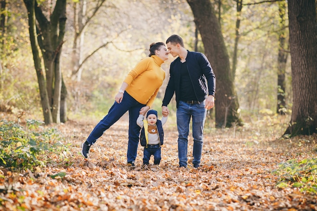 Jeune belle famille marchant main dans la main par le parc de la ville. saison de l'automne. famille heureuse et leurs fils se promènent dans le parc de l'automne et passent un bon moment.