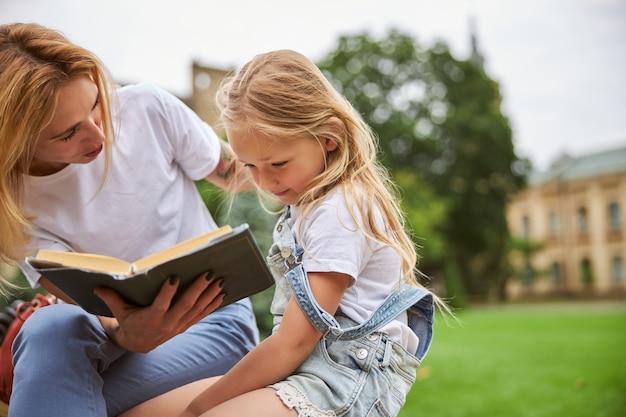 Jeune belle famille passant du temps sur l'herbe verte dans le parc avec un gros livre