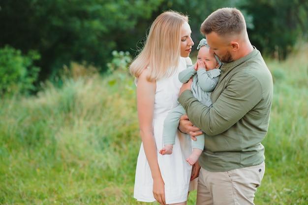 Jeune belle famille avec une petite fille câlin, embrasse et marche dans la nature au coucher du soleil. photo d'une famille avec un petit enfant dans la nature.